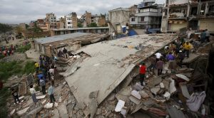 People gather near a collapsed house after a major earthquake in Kathmandu, Nepal April 25, 2015. A shallow earthquake measuring 7.9 magnitude struck west of the ancient Nepali capital of Kathmandu on Saturday, killing more than 100 people, injuring hundreds and leaving a pall over the valley, doctors and witnesses said. REUTERS/Navesh Chitrakar
