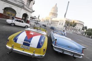 A car with a Cuban flag is parked near Cuban Capitol in Havana December 18, 2014. Cuban President Raul Castro hailed a landmark exchange of prisoners with the United States on Wednesday and praised U.S. President Barack Obama as the two countries agreed to normalize relations after more than five decades of hostility. REUTERS/Enrique De La Osa (CUBA - Tags: POLITICS SOCIETY)